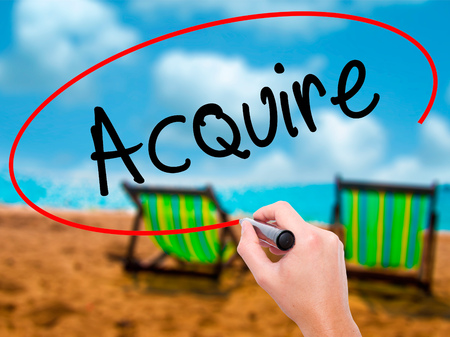 acquire: Man Hand writing Acquire with black marker on visual screen. Isolated on sunbed on the beach. Business, technology, internet concept. Stock Photo Stock Photo