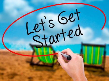 Man Hand writing Lets Get Started  with black marker on visual screen. Isolated on sunbed on the beach. Business, technology, internet concept. Stock Photo