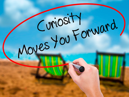 Man Hand writing Curiosity Moves You Forward with black marker on visual screen. Isolated on sunbed on the beach. Business, technology, internet concept. Stock Photo