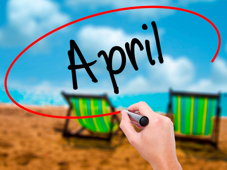 Man Hand writing  April  with black marker on visual screen. Isolated on sunbed on the beach. Business, technology, internet concept. Stock Photo Stock Photo