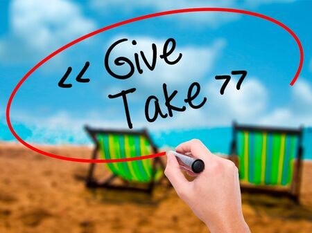 Man Hand writing Give - Take with black marker on visual screen. Isolated on sunbed on the beach. Business, technology, internet concept. Stock Photo