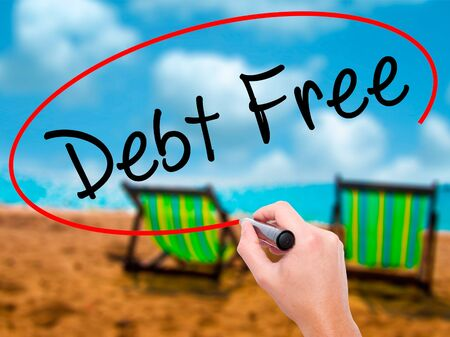 Man Hand writing Debt Free with black marker on visual screen. Isolated on sunbed on the beach. Business, technology, internet concept. Stock Photo Stock Photo