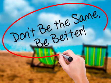 Man Hand writing Dont Be the Same, Be Better! with black marker on visual screen. Isolated on sunbed on the beach. Business, technology, internet concept. Stock Photo