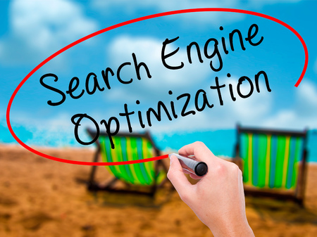Man Hand writing Search Engine Optimization with black marker on visual screen. Isolated on sunbed on the beach. Business, technology, internet concept. Stock Image
