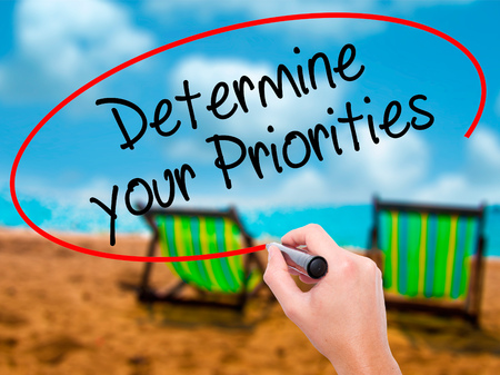Man Hand writing Determine your Priorities with black marker on visual screen. Isolated on sunbed on the beach. Business, technology, internet concept. Stock Photo