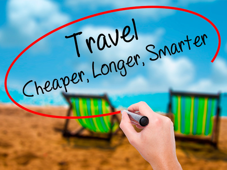smarter: Man Hand writing Travel Cheaper Longer Smarter  with black marker on visual screen. Isolated on sunbed on the beach. Business, technology, internet concept. Stock Photo