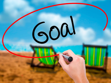 owning: Man Hand writing Goal  with black marker on visual screen. Isolated on sunbed on the beach. Business, technology, internet concept. Stock Photo