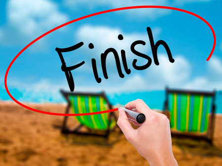 complete crossing: Man Hand writing  Finish with black marker on visual screen. Isolated on sunbed on the beach. Business, technology, internet concept. Stock Photo