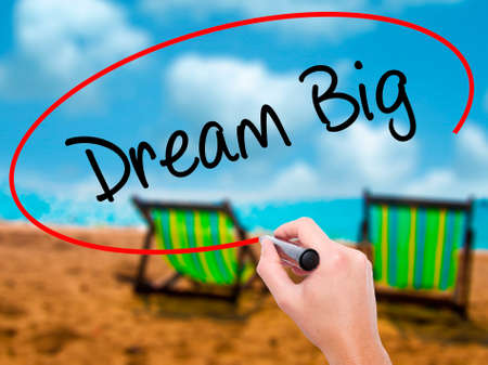 Man Hand writing Dream Big  with black marker on visual screen. Isolated on sunbed on the beach. Business, technology, internet concept. Stock Photo