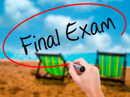 Man Hand writing Final Exam with black marker on visual screen. Isolated on sunbed on the beach. Business, technology, internet concept. Stock Photo