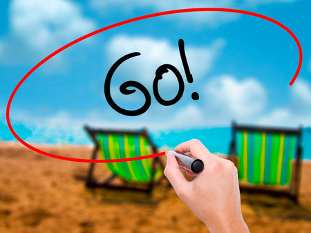 working ethic: Man Hand writing Go! with black marker on visual screen. Isolated on sunbed on the beach. Business, technology, internet concept. Stock Photo Stock Photo