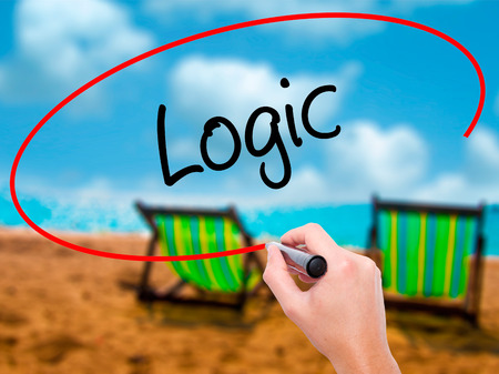 Man Hand writing Logic with black marker on visual screen. Isolated on sunbed on the beach. Business, technology, internet concept.