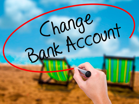 Man Hand writing Change Bank Account with black marker on visual screen. Isolated on sunbed on the beach. Business, technology, internet concept. Stock Photo Stock Photo