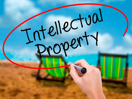 arms trade: Man Hand writing Intellectual Property with black marker on visual screen. Isolated on sunbed on the beach. Business, technology, internet concept. Stock Photo Stock Photo