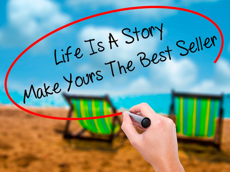 owning: Man Hand writing Life Is A Story Make Yours The Best Seller with black marker on visual screen. Isolated on sunbed on the beach. Business, technology, internet concept. Stock Photo