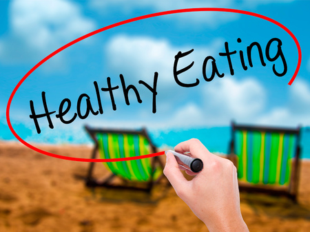 Man Hand writing Healthy Eating with black marker on visual screen. Isolated on sunbed on the beach. Life, technology, internet concept. Stock Image Stock Photo