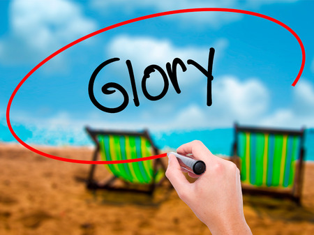 keys to heaven: Man Hand writing Glory with black marker on visual screen. Isolated on sunbed on the beach. Business, technology, internet concept. Stock Photo