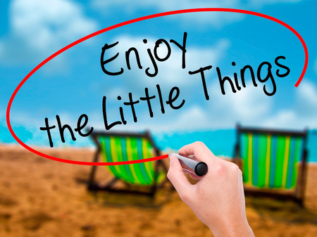 Man Hand writing  Enjoy the Little Things with black marker on visual screen. Isolated on sunbed on the beach. Business, technology, internet concept. Stock Photo Stock Photo