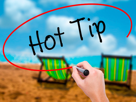 Man Hand writing Hot Tip with black marker on visual screen. Isolated on sunbed on the beach. Business, technology, internet concept. Stock Photo