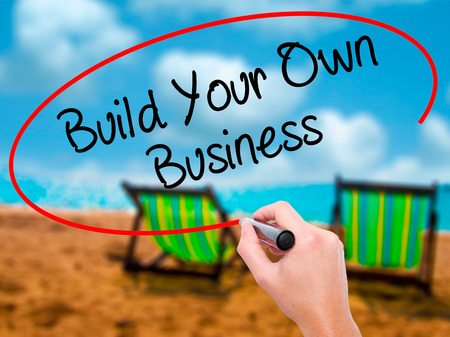 Man Hand writing Build Your Own Business with black marker on visual screen. Isolated on sunbed on the beach. Business, technology, internet concept. Stock  Photo Stock Photo