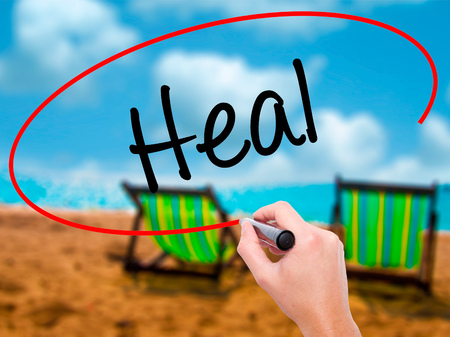 Man Hand writing  Heal  with black marker on visual screen. Isolated on sunbed on the beach. Business, technology, internet concept. Stock Photo