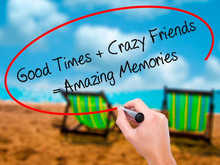 Man Hand writing Good Times + Crazy Friends = Amazing Memories with black marker on visual screen. Isolated on sunbed on the beach. Business, technology, internet concept. Stock Photo
