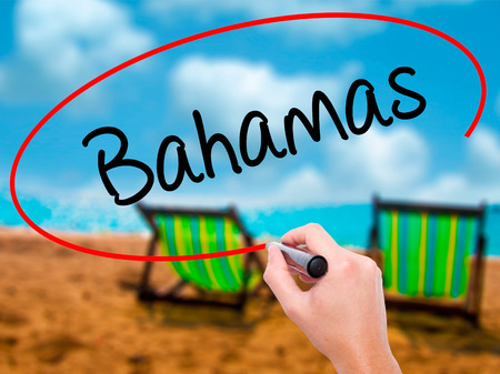 Man Hand writing Bahamas with black marker on visual screen. Isolated on sunbed on the beach. Business, technology, internet concept. Stock Photo