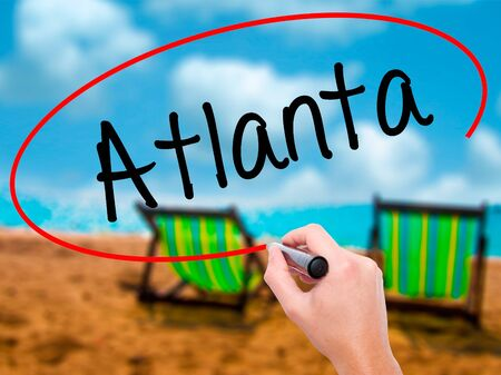 Man Hand writing Atlanta with black marker on visual screen. Isolated on sunbed on the beach. Business, technology, internet concept. Stock Photo