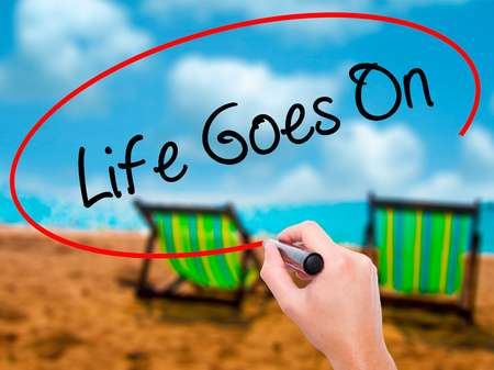 jargon: Man Hand writing Life Goes On with black marker on visual screen. Isolated on sunbed on the beach. Business, technology, internet concept. Stock Photo Stock Photo