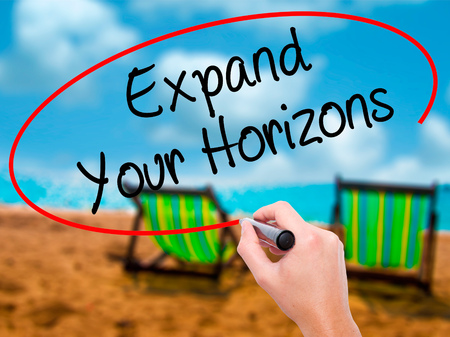 Man Hand writing  Expand Your Horizons  with black marker on visual screen. Isolated on sunbed on the beach. Business, technology, internet concept. Stock Photo Stock Photo