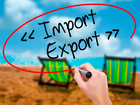 Man Hand writing Import - Export with black marker on visual screen. Isolated on sunbed on the beach. Business, technology, internet concept. Stock Photo
