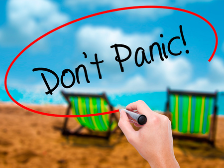 Man Hand writing Dont Panic! with black marker on visual screen. Isolated on sunbed on the beach. Business, technology, internet concept. Stock Photo