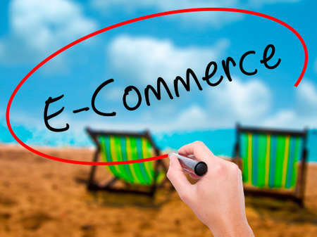 Man Hand writing E-Commerce with black marker on visual screen. Isolated on sunbed on the beach. Business, technology, internet concept. Stock Image Stock Photo