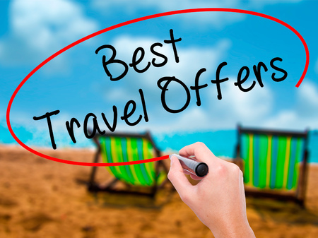 Man Hand writing Best Travel Offers  with black marker on visual screen. Isolated on sunbed on the beach. Travel technology, internet concept. Stock Image