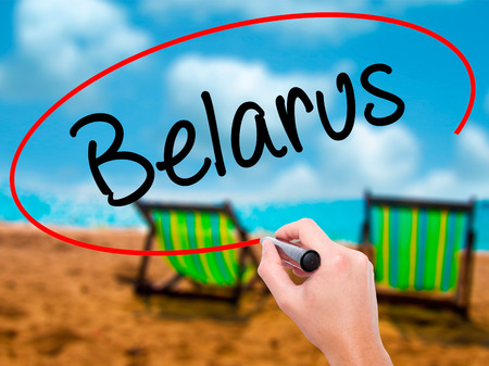 Man Hand writing Belarus  with black marker on visual screen. Isolated on sunbed on the beach. Business, technology, internet concept. Stock  Photo