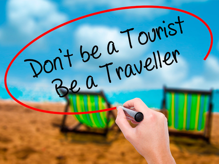 Man Hand writing Dont be a Tourist Be a Traveller  with black marker on visual screen. Isolated on sunbed on the beach. Business, technology, internet concept. Stock Photo Stock Photo