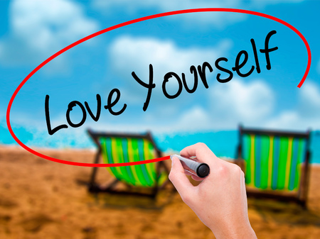 egoistic: Man Hand writing Love Yourself with black marker on visual screen. Isolated on sunbed on the beach. Business, technology, internet concept. Stock Photo Stock Photo