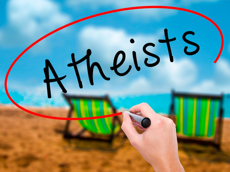 atheist: Man Hand writing Atheists with black marker on visual screen. Isolated on sunbed on the beach. Business, technology, internet concept. Stock Image Stock Photo
