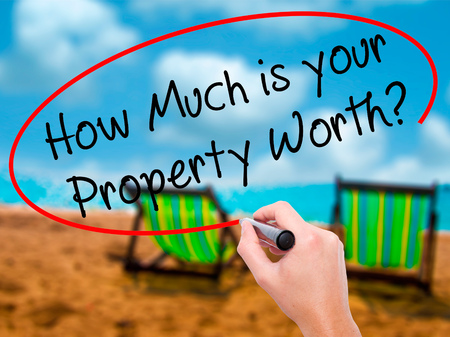 Man Hand writing How Much is your Property Worth? with black marker on visual screen. Isolated on sunbed on the beach. Business, technology, internet concept. Stock Image