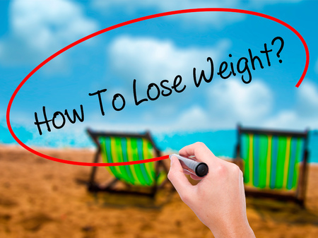 Man Hand writing How To Lose Weight? with black marker on visual screen. Isolated on sunbed on the beach. Business, technology, internet concept.