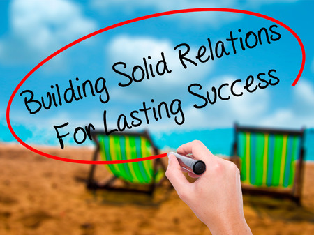lasting: Man Hand writing Building Solid Relations For Lasting Success with black marker on visual screen. Isolated on sunbed on the beach. Business, technology, internet concept. Stock Image