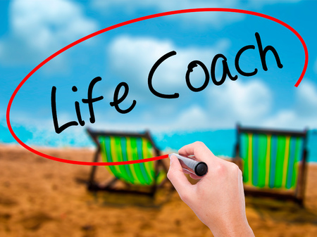 learning new skills: Man Hand writing Life Coach with black marker on visual screen. Isolated on sunbed on the beach. Business, technology, internet concept. Stock Photo