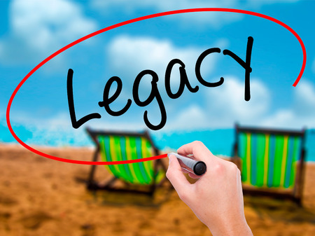 impression: Man Hand writing Legacy with black marker on visual screen. Isolated on sunbed on the beach. Business, technology, internet concept. Stock Photo