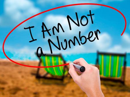 Escritura de la mano del hombre no soy un número con marcador negro en la pantalla visual. Aislado en sunbed en la playa. Negocios, tecnología, concepto de internet. Foto de stock