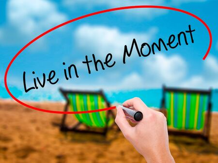 Man Hand writing Live in the Moment with black marker on visual screen. Isolated on sunbed on the beach. Business, technology, internet concept. Stock Photo