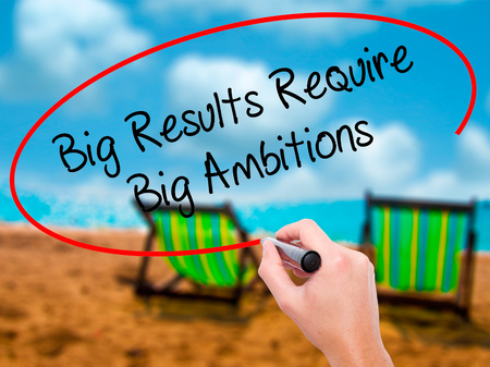 ambitions: Man Hand writing Big Results Require Big Ambitions with black marker on visual screen. Isolated on sunbed on the beach. Business, technology, internet concept. Stock Photo