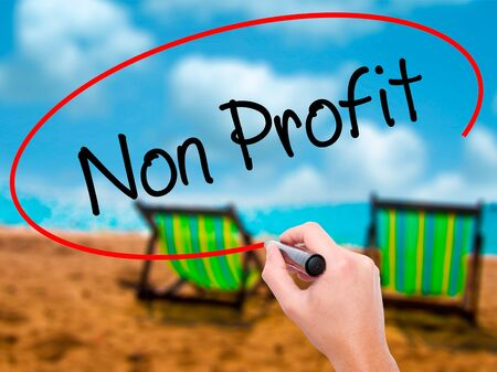 non stock: Man Hand writing Non Profit with black marker on visual screen. Isolated on sunbed on the beach. Business, technology, internet concept. Stock Photo