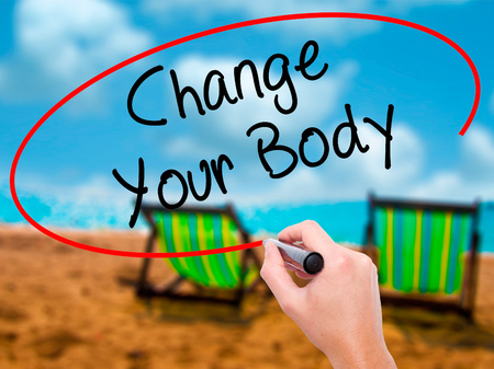 muscle gain: Man Hand writing Change Your Body with black marker on visual screen. Isolated on sunbed on the beach. Business, technology, internet concept. Stock Photo