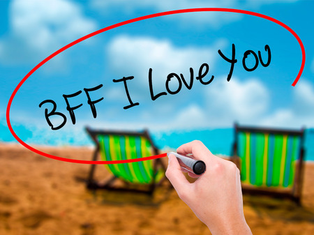 nota: Man Hand writing BFF I Love You with black marker on visual screen. Isolated on sunbed on the beach. Business, technology, internet concept.