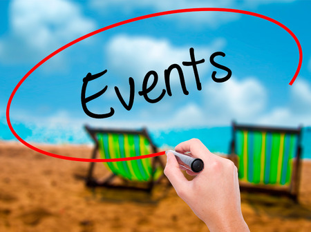 important date: Man Hand writing Events with black marker on visual screen. Isolated on sunbed on the beach. Business, technology, internet concept. Stock Photo